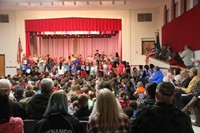 far shot of children singing at veterans day assembly