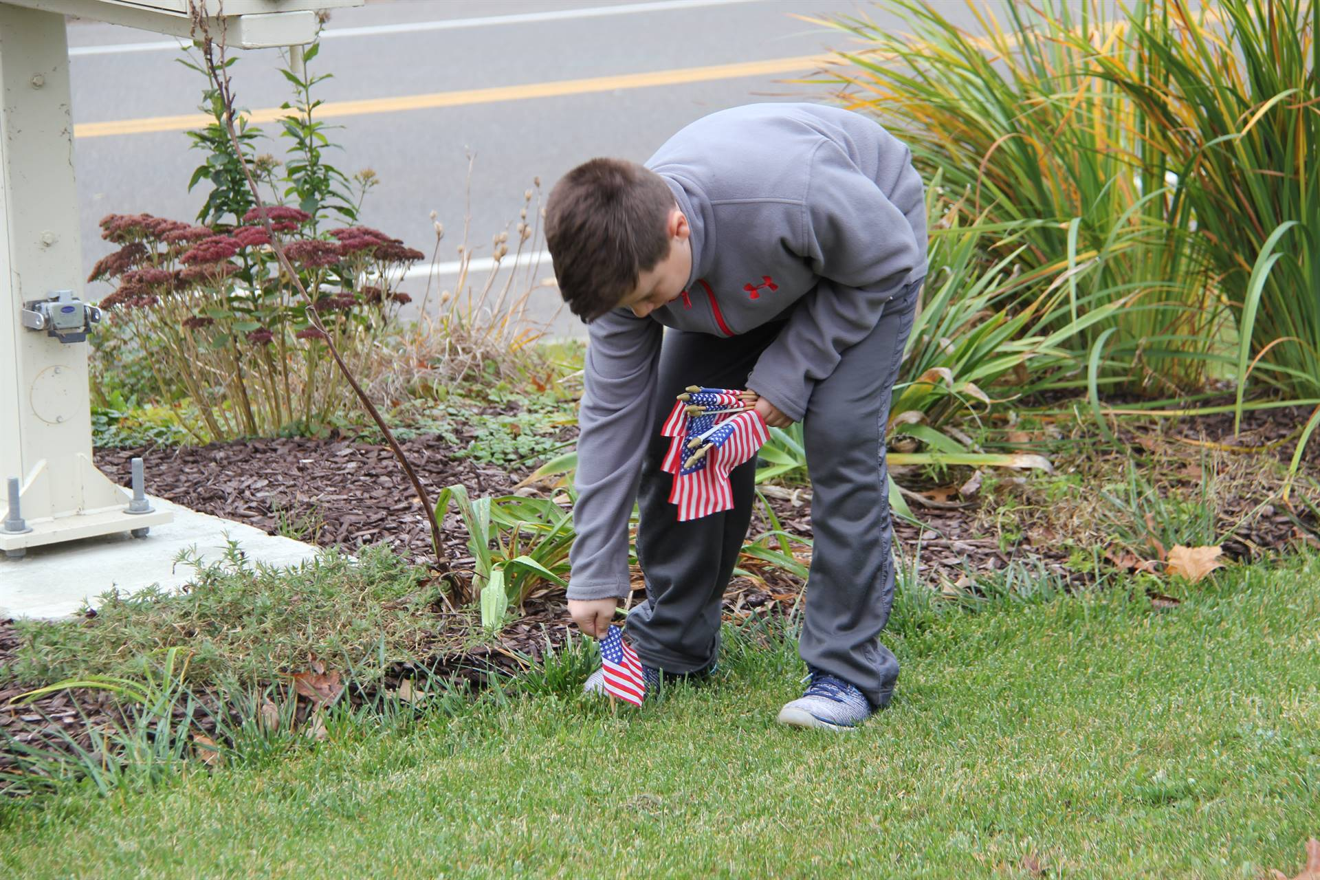 boy planting flag in grass