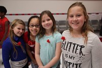four girls smile wearing red poppies in recognition of veterans