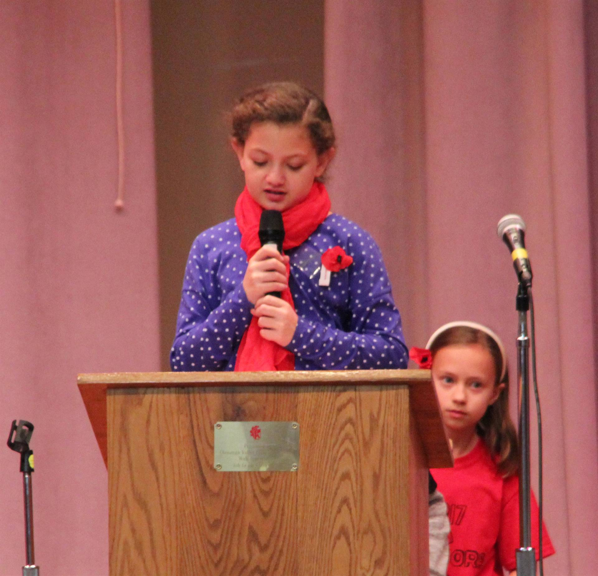 girl talking at podium at veterans day assembly