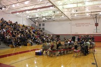 family members in stands watching students receive fall sports awards