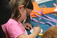 girl coloring in olympic medal