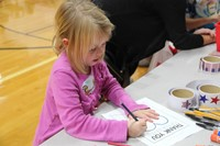 girl coloring in thank you to veterans page
