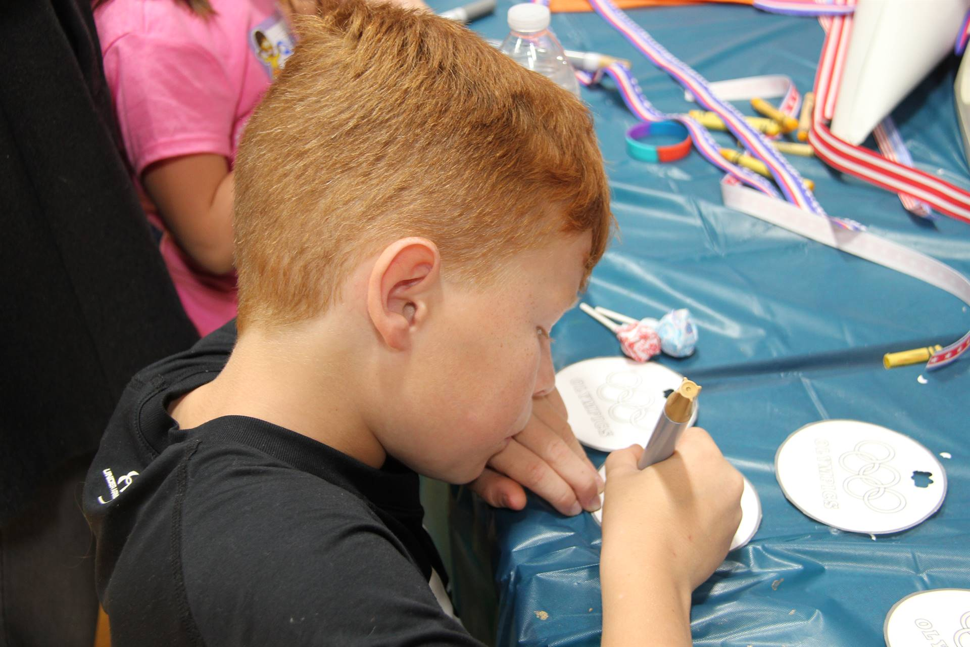 boy coloring in olympic medal at humanities night