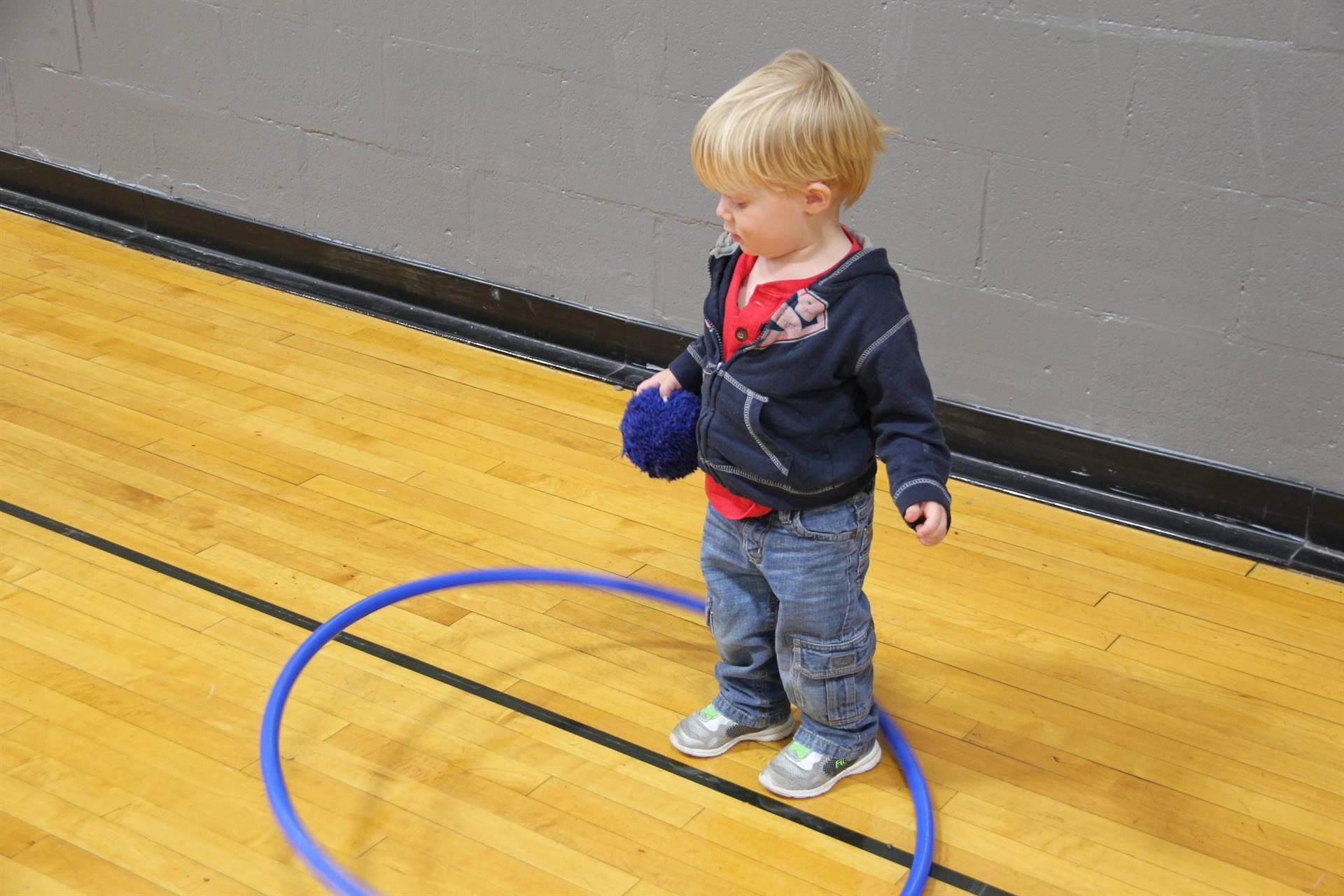 little boy hula hoops while wearing a ball