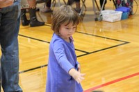 little girl throwing a ball as part of humanities night game