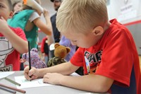 boy coloring picture of veteran at humanities night