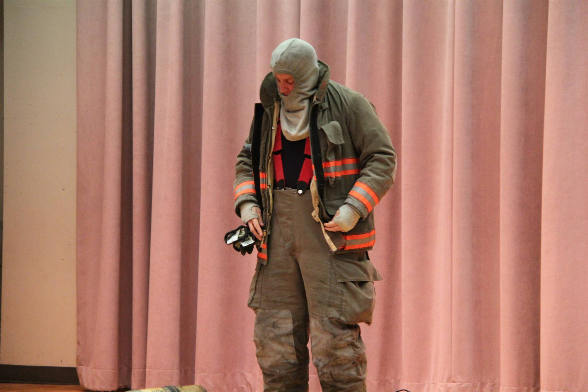 firefighter demonstrates putting on his equipment