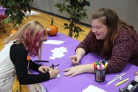 student helping younger student with activity at humanities night