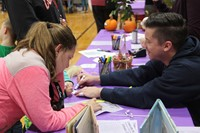 students working with teacher at musical table at humanities night