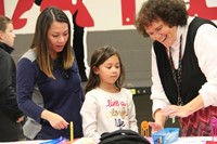 teacher helping student and parent at humanities night table
