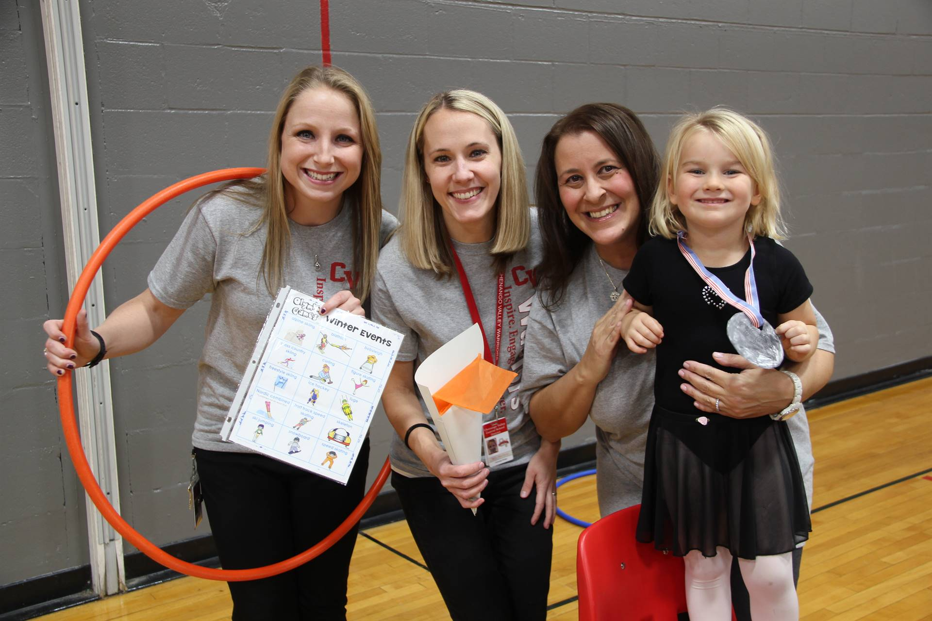 three teachers and student smile at olympics activity at humanities night