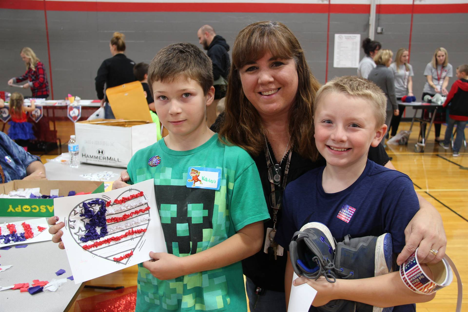 woman and two boys smile one boy holding american flag heart
