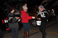 people handing out candy for trunk or treat event