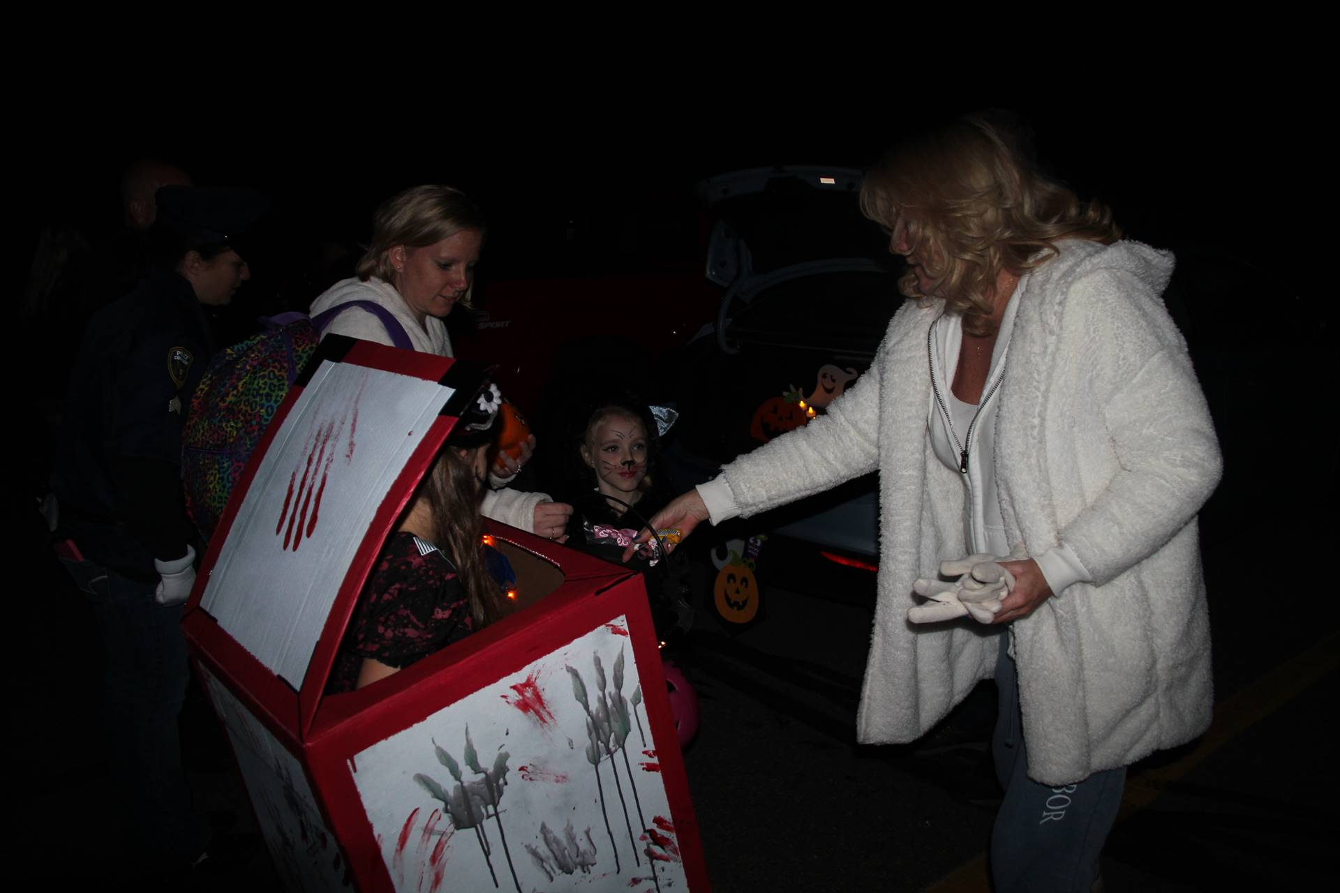 person handing out candy at trunk or treat event