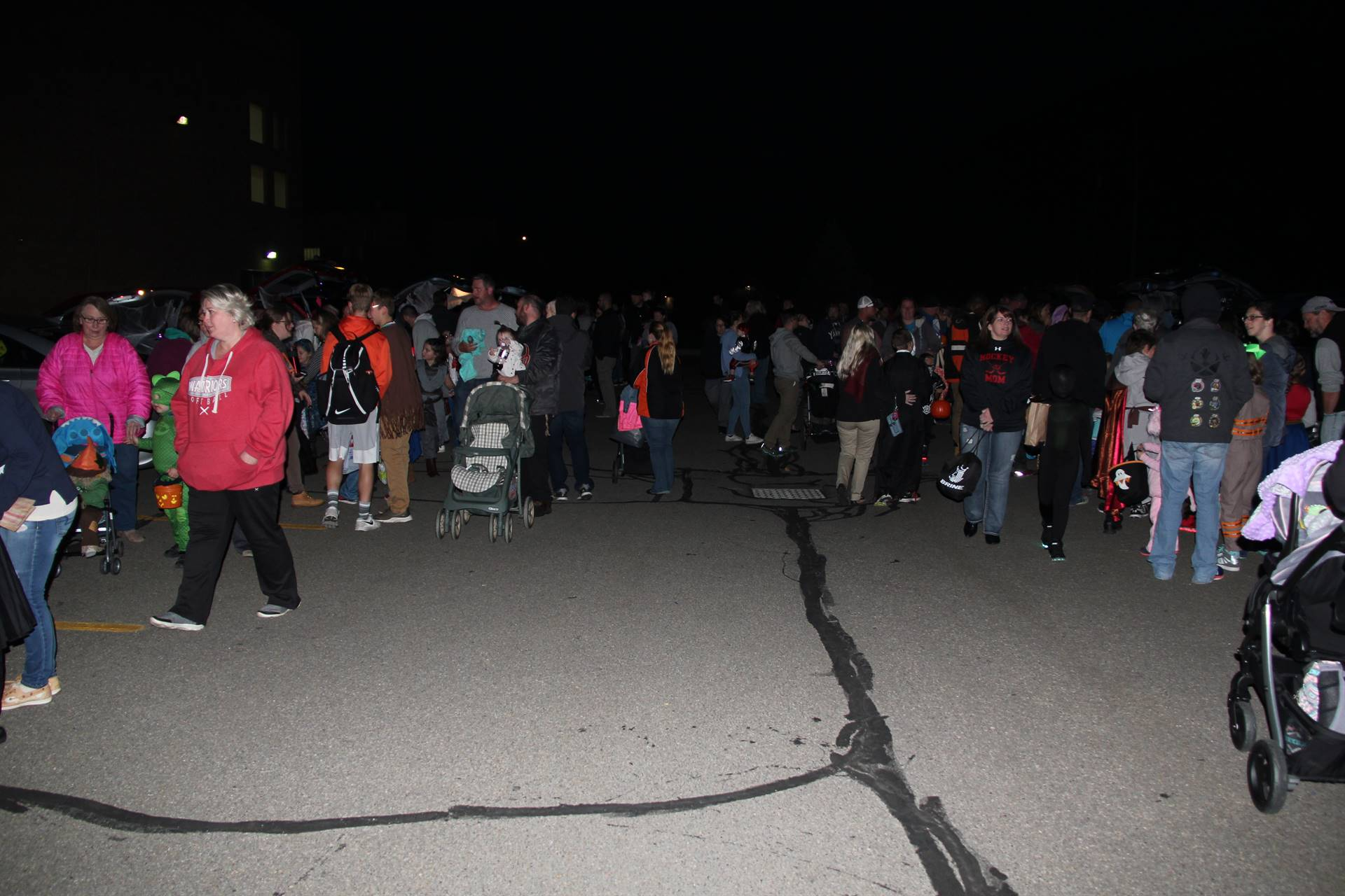 wide shot of people outside for trunk or treat event
