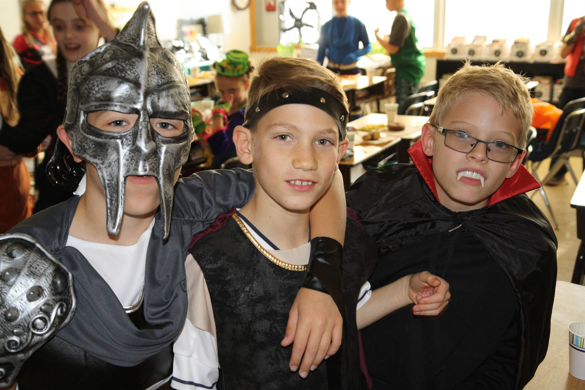 three boy students dressed in halloween costumes