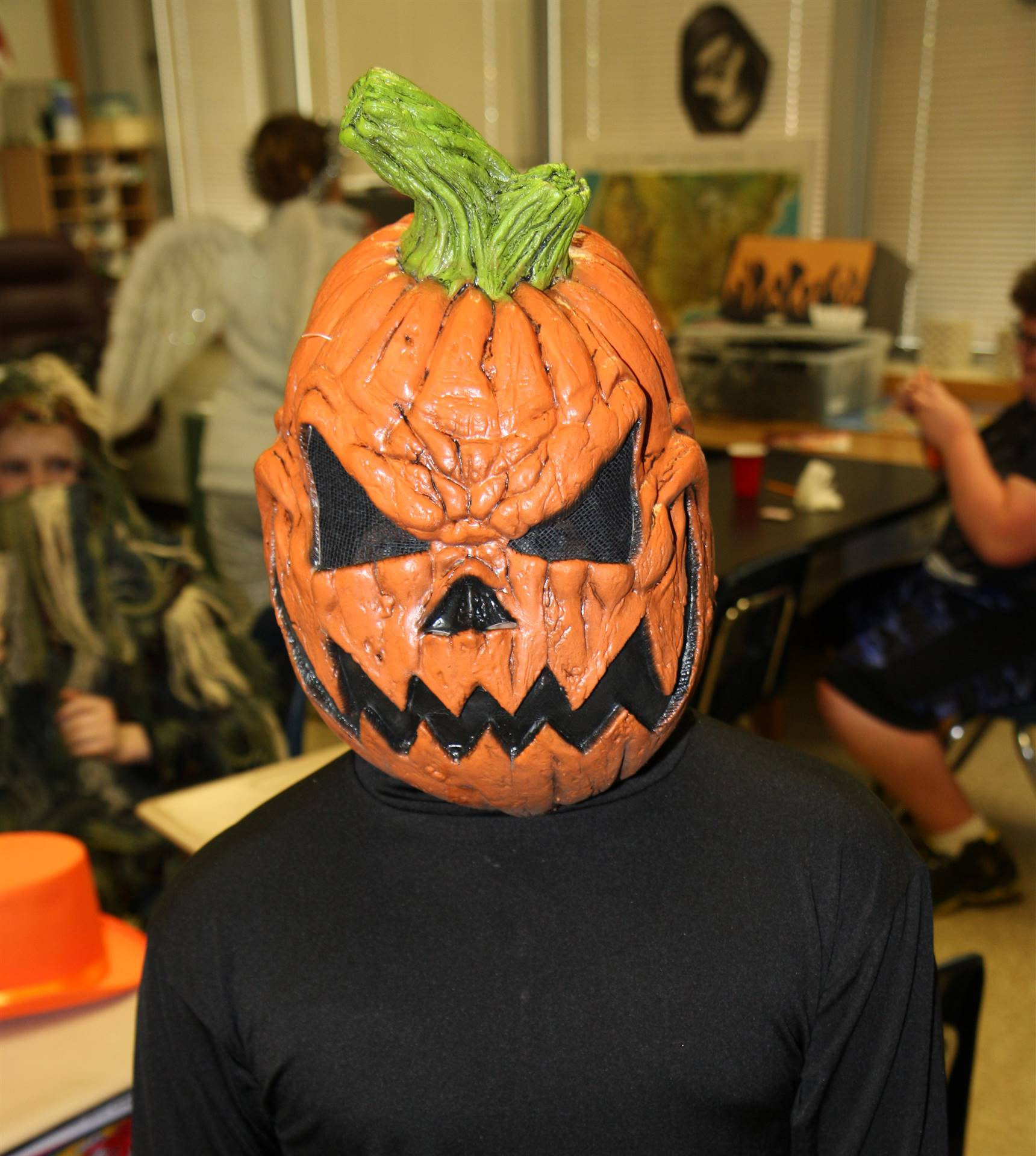 student dressed in spooky pumpkin head costume