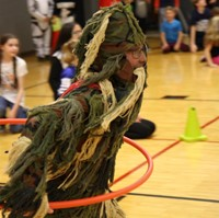 student dressed as grass monster hula hooping