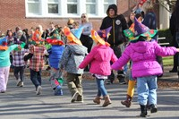 pre school students walking with scarecrow hats they made on