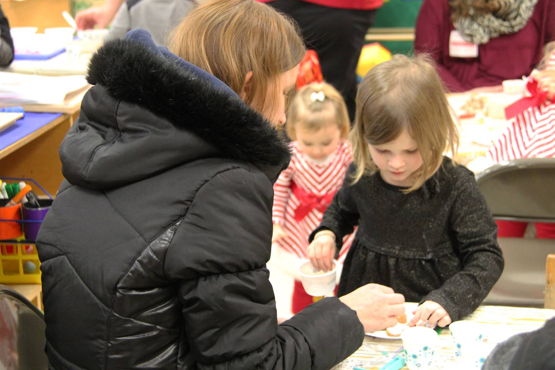 woman helping girl decorate gingerbread cookie