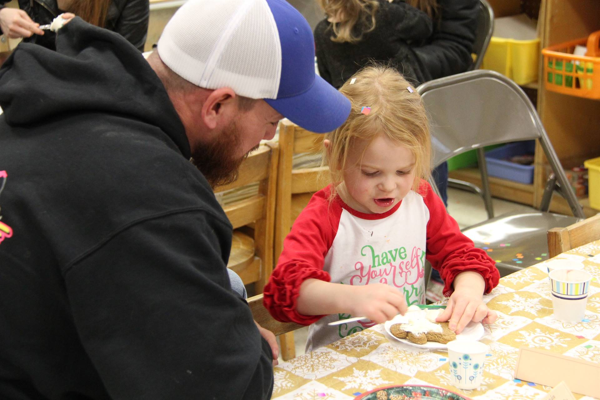 girl decorating gingerbread cookie with man
