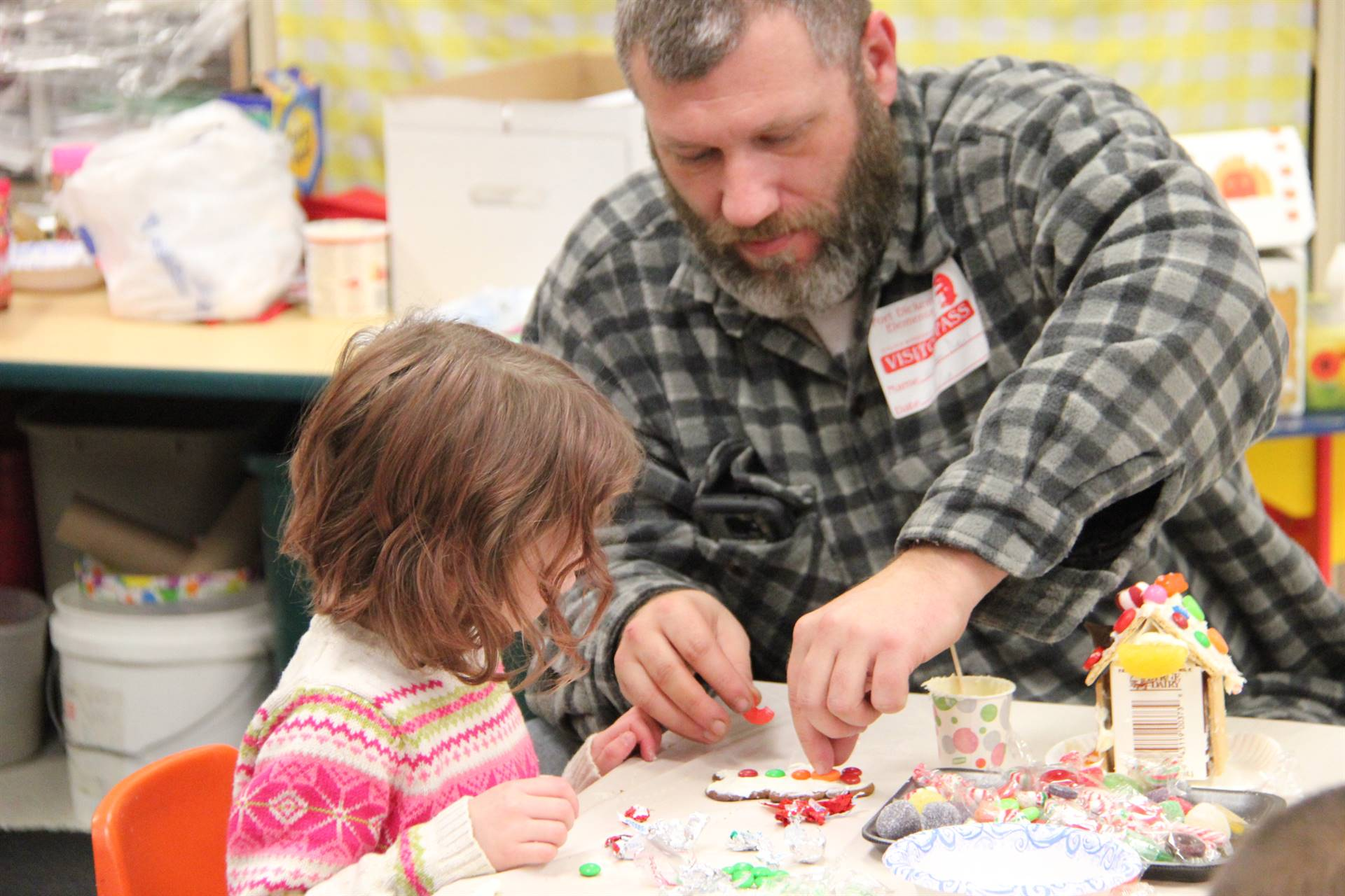 man helping girl decorate gingerbread cookie