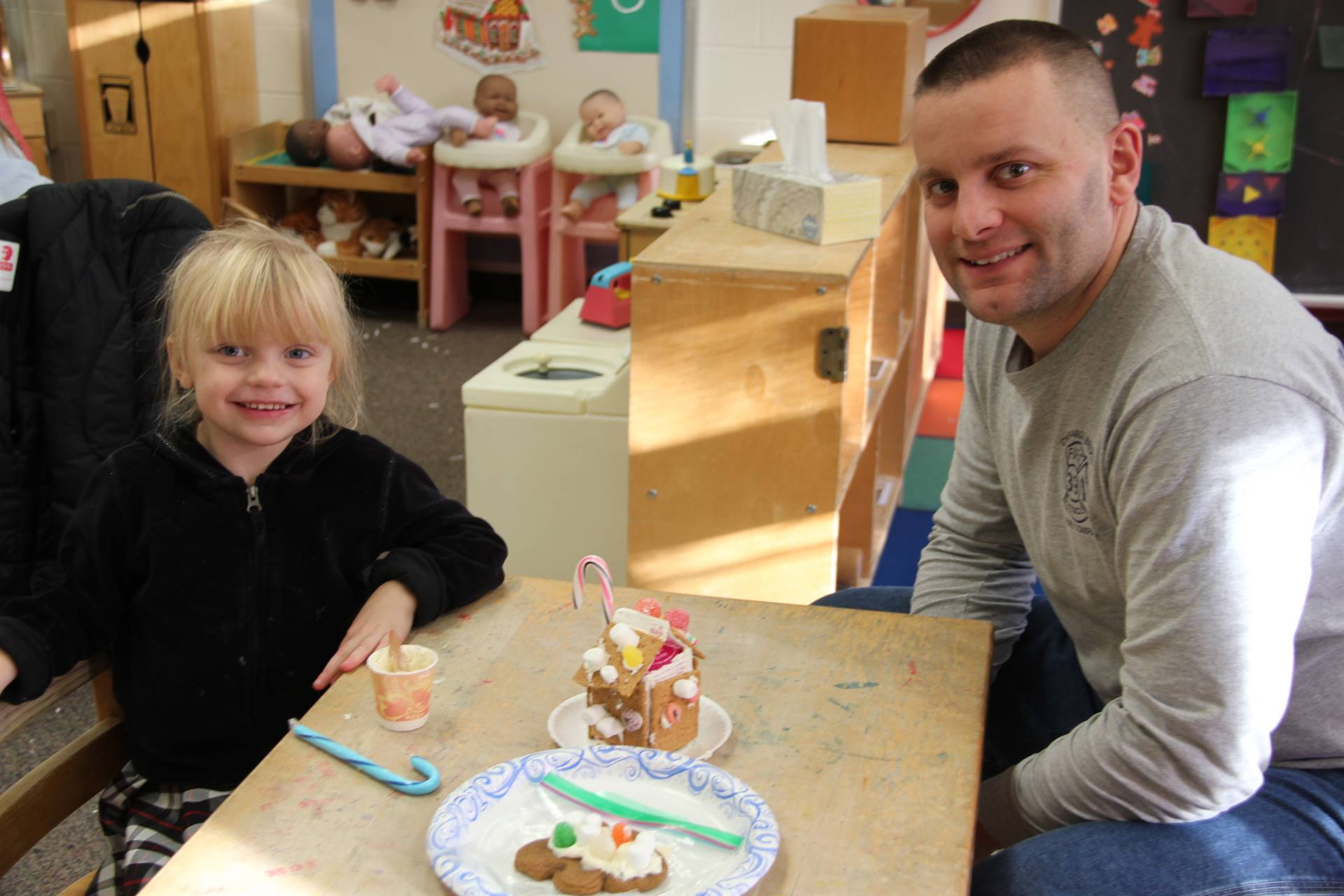 man and girl smiling next to gingerbread house