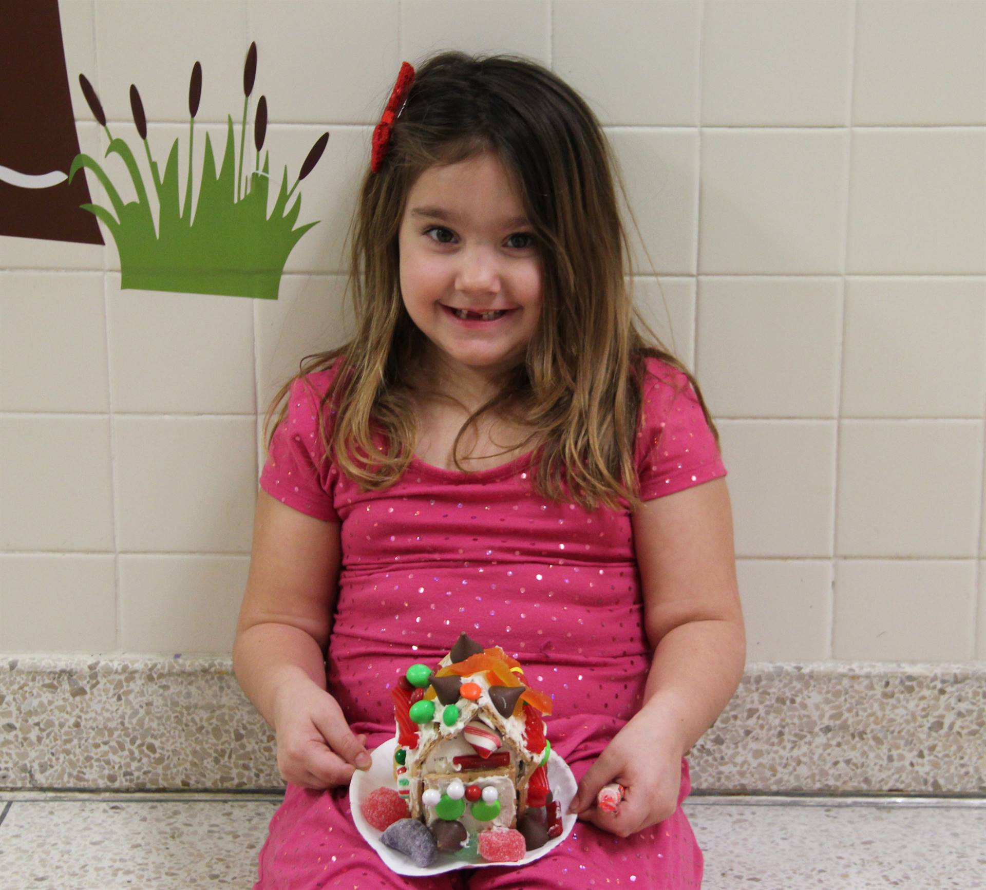 girl holding decorated gingerbread house