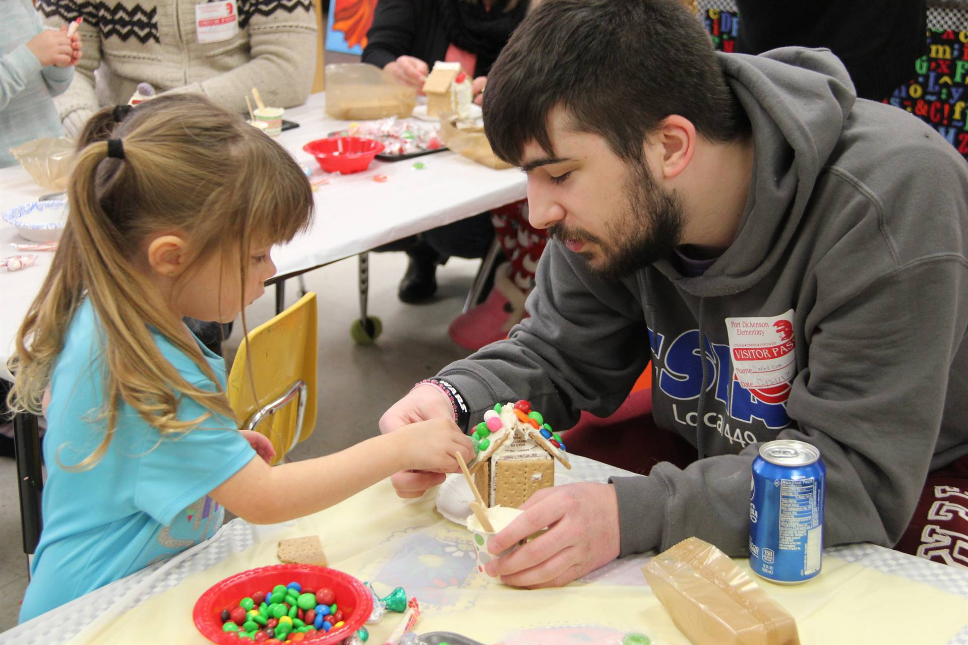 man helping girl decorate gingerbread house