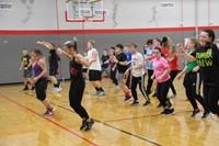 wide shot of students zumba dancing