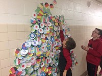students putting holiday ornament on wall