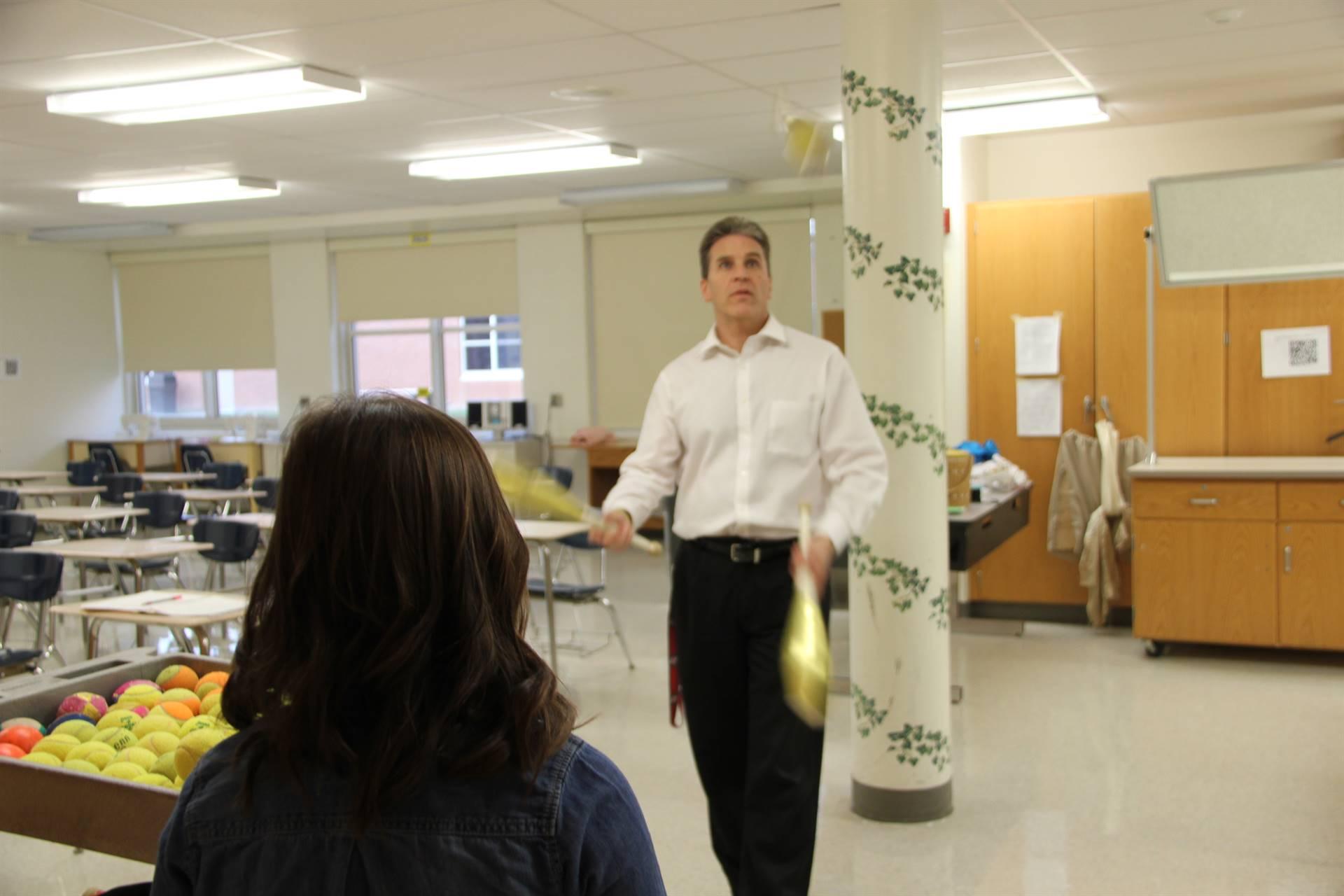 student watching teacher juggle