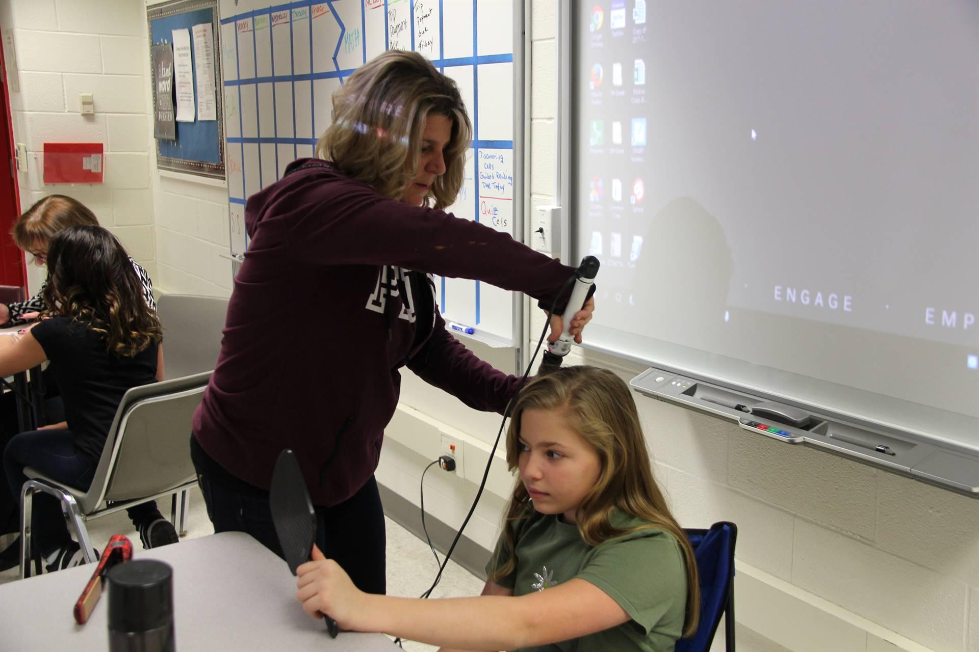 teacher curling students hair