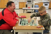 student and teacher playing chess