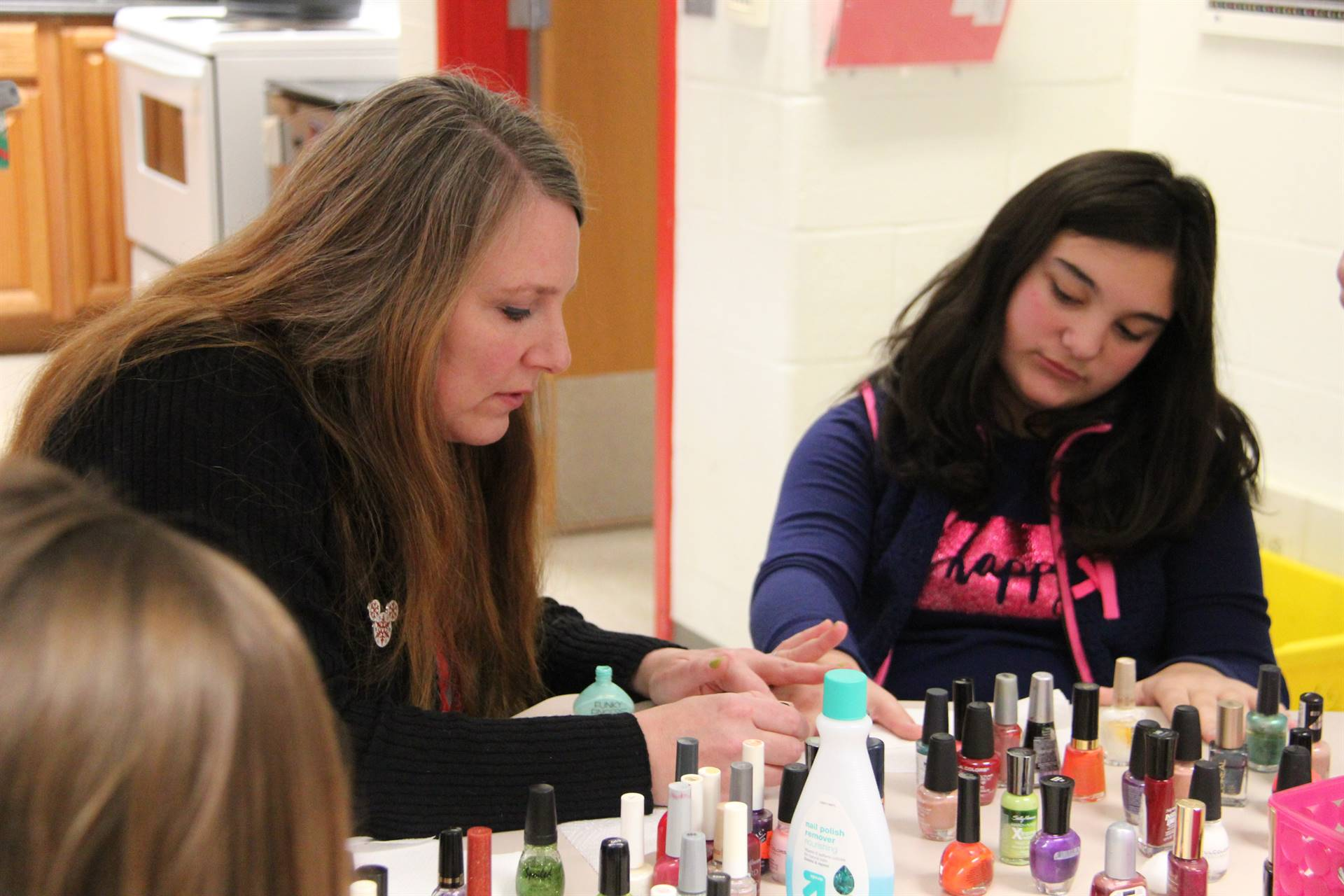 teacher painting students nails