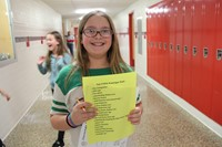 student smiling with scavenger hunt paper