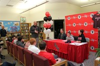 wide shot of student signing in library with mister tomm talking