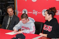 student signing paper two adults sitting with him watch