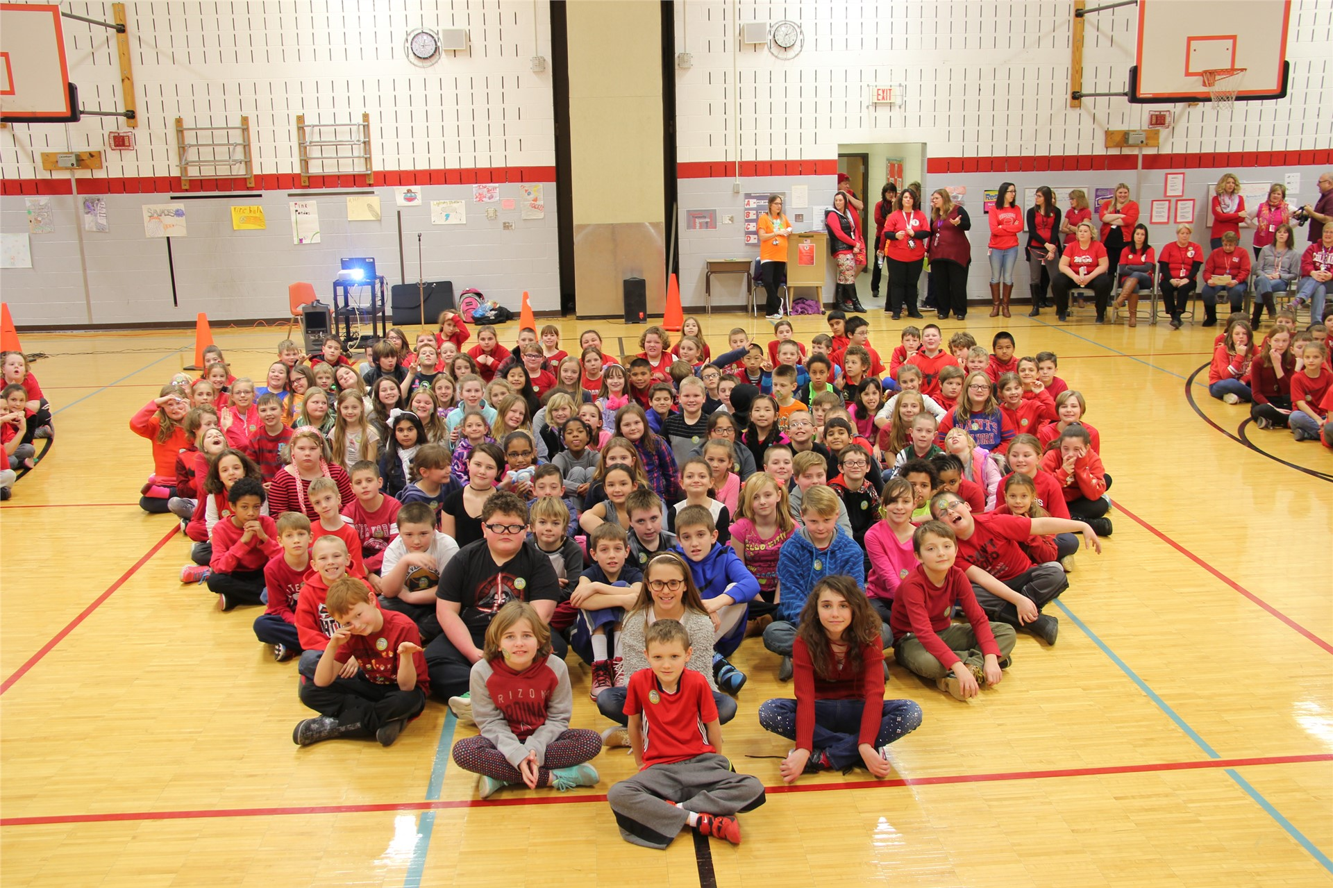 large group of students sit in heart shape 2