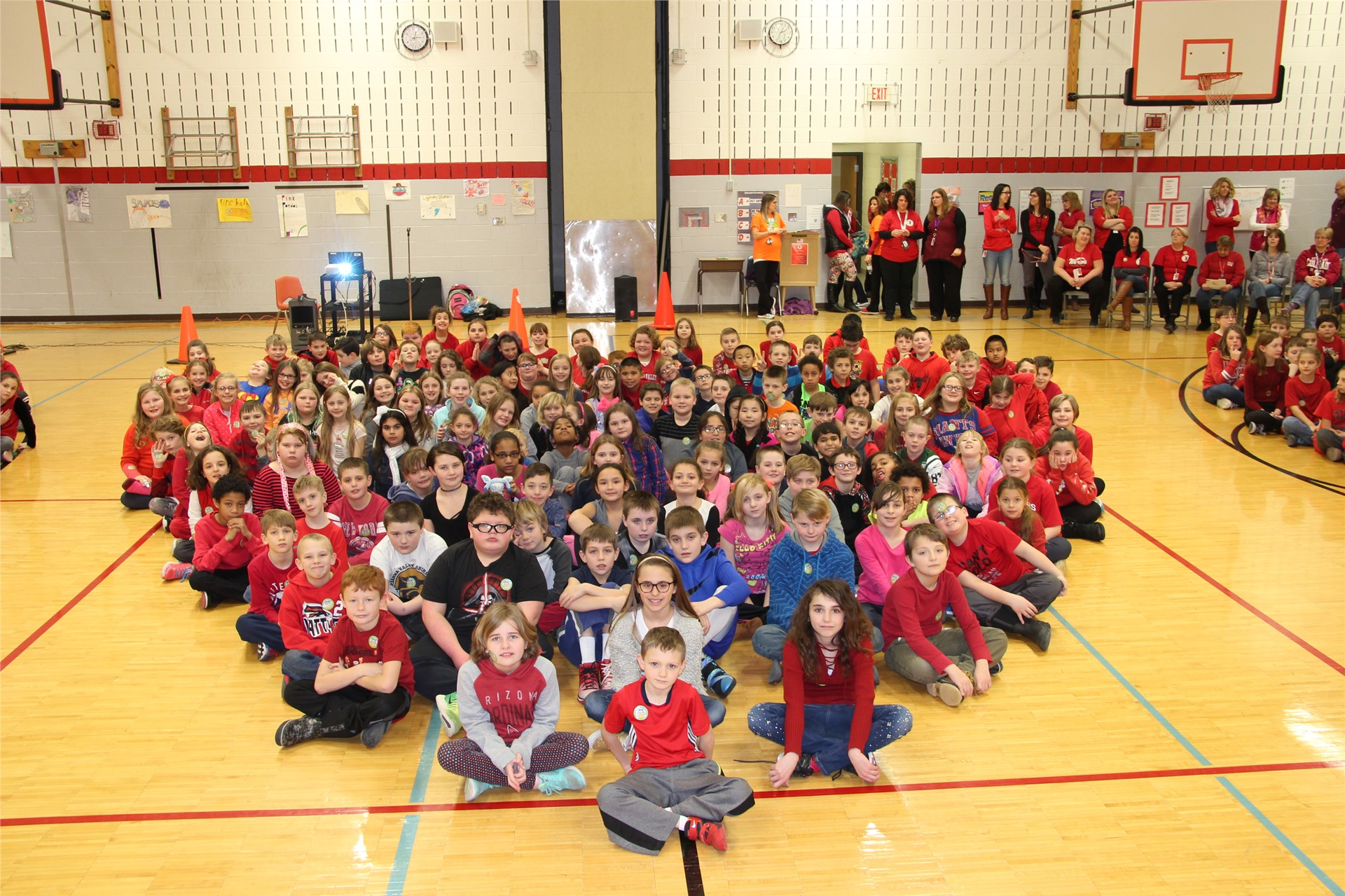 large group of students sit in heart shape 3