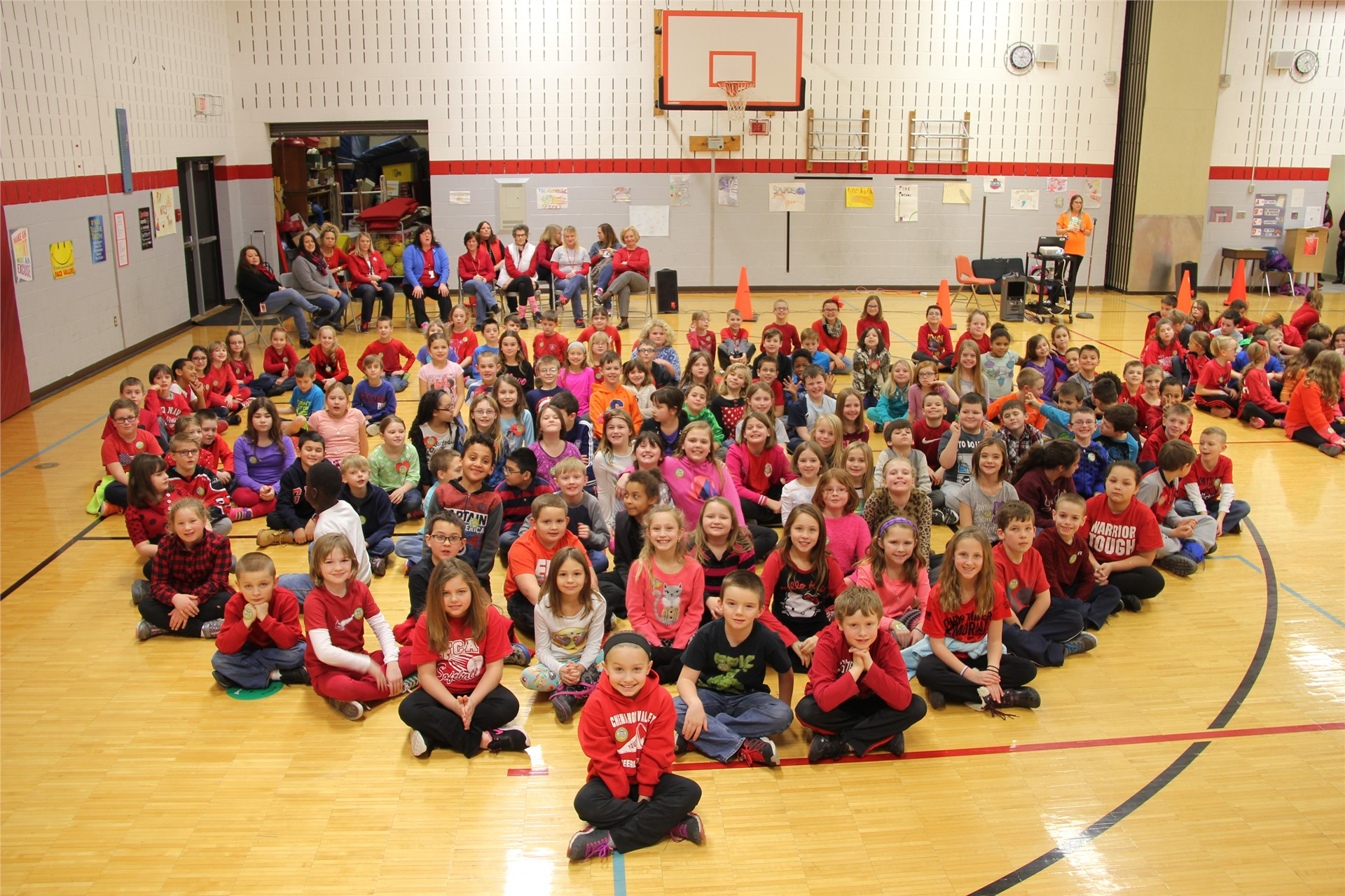 large group of students sit in heart shape 7