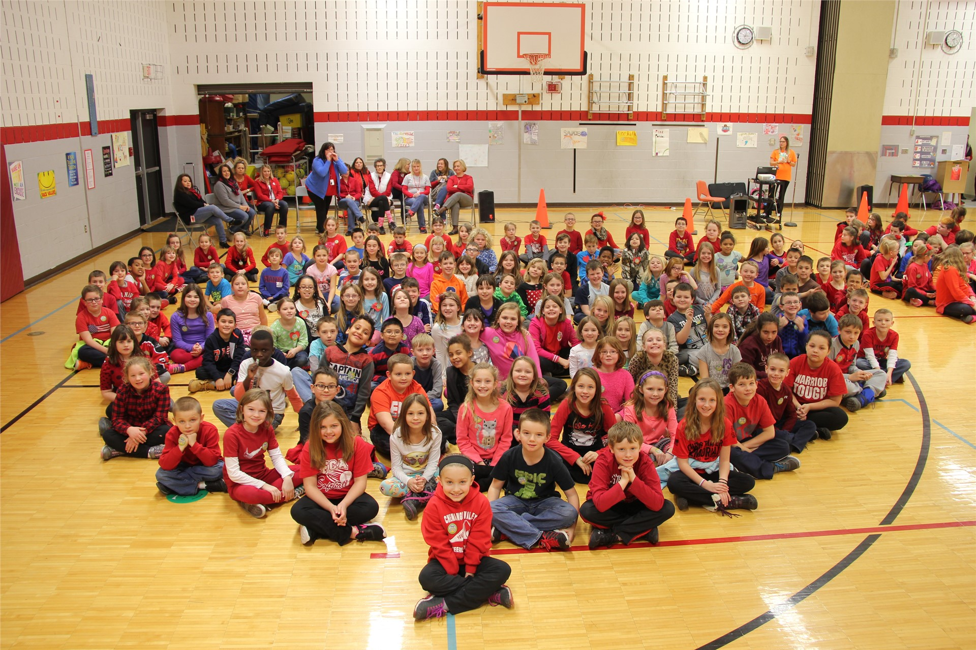 large group of students sit in heart shape 8