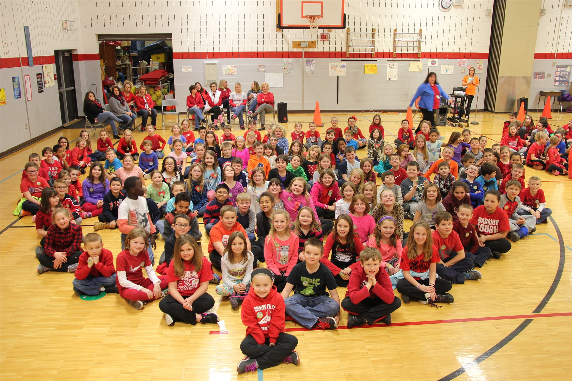 large group of students sit in heart shape 11