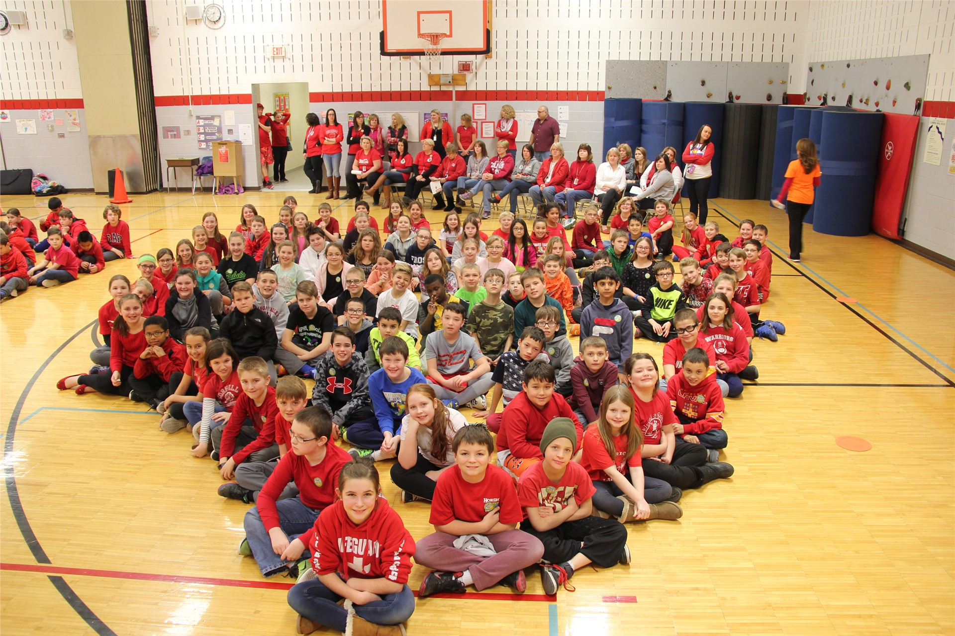 large group of students sit in heart shape 14