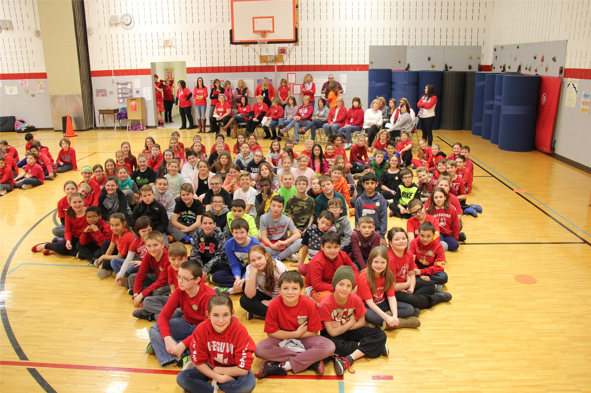 large group of students sit in heart shape 15