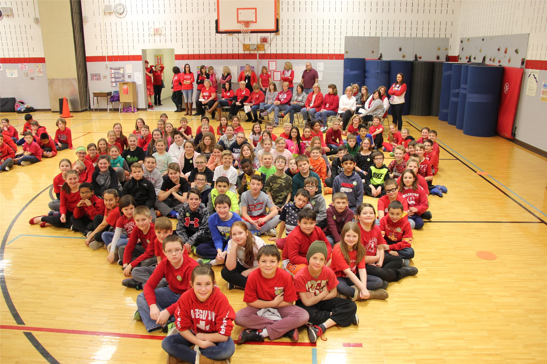 large group of students sit in heart shape 12