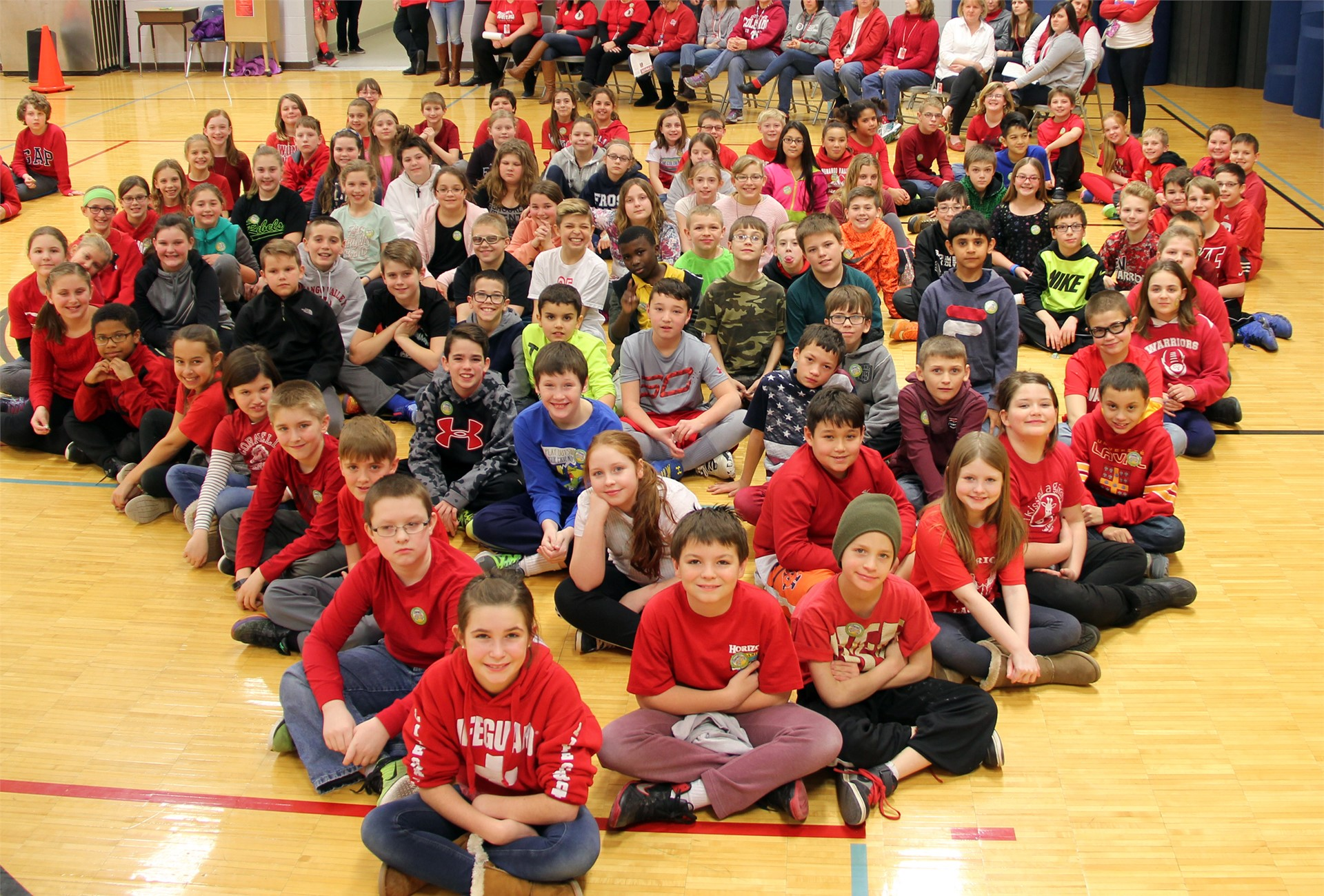 large group of students sit in heart shape 13