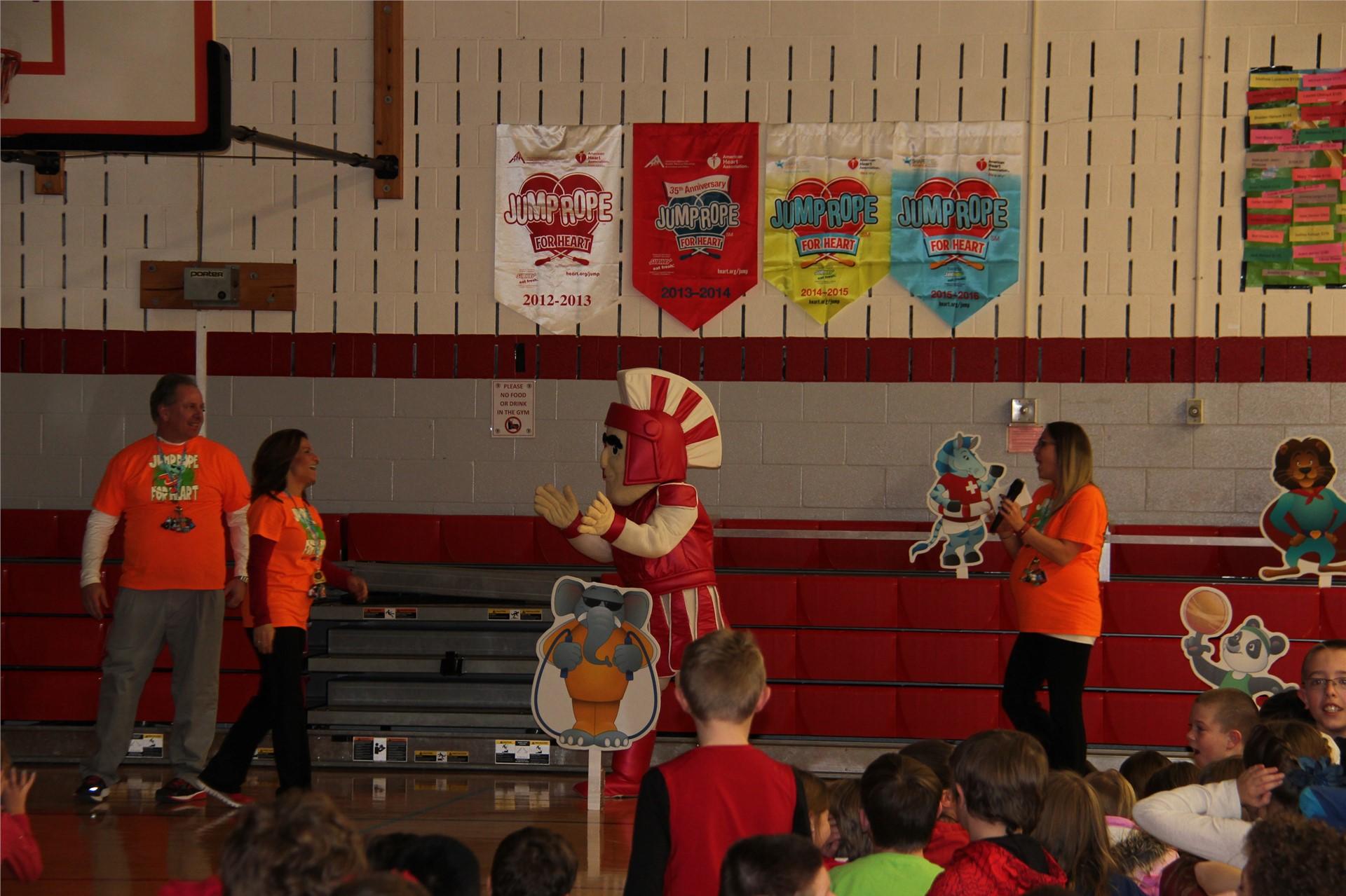 teachers stand with warrior mascot