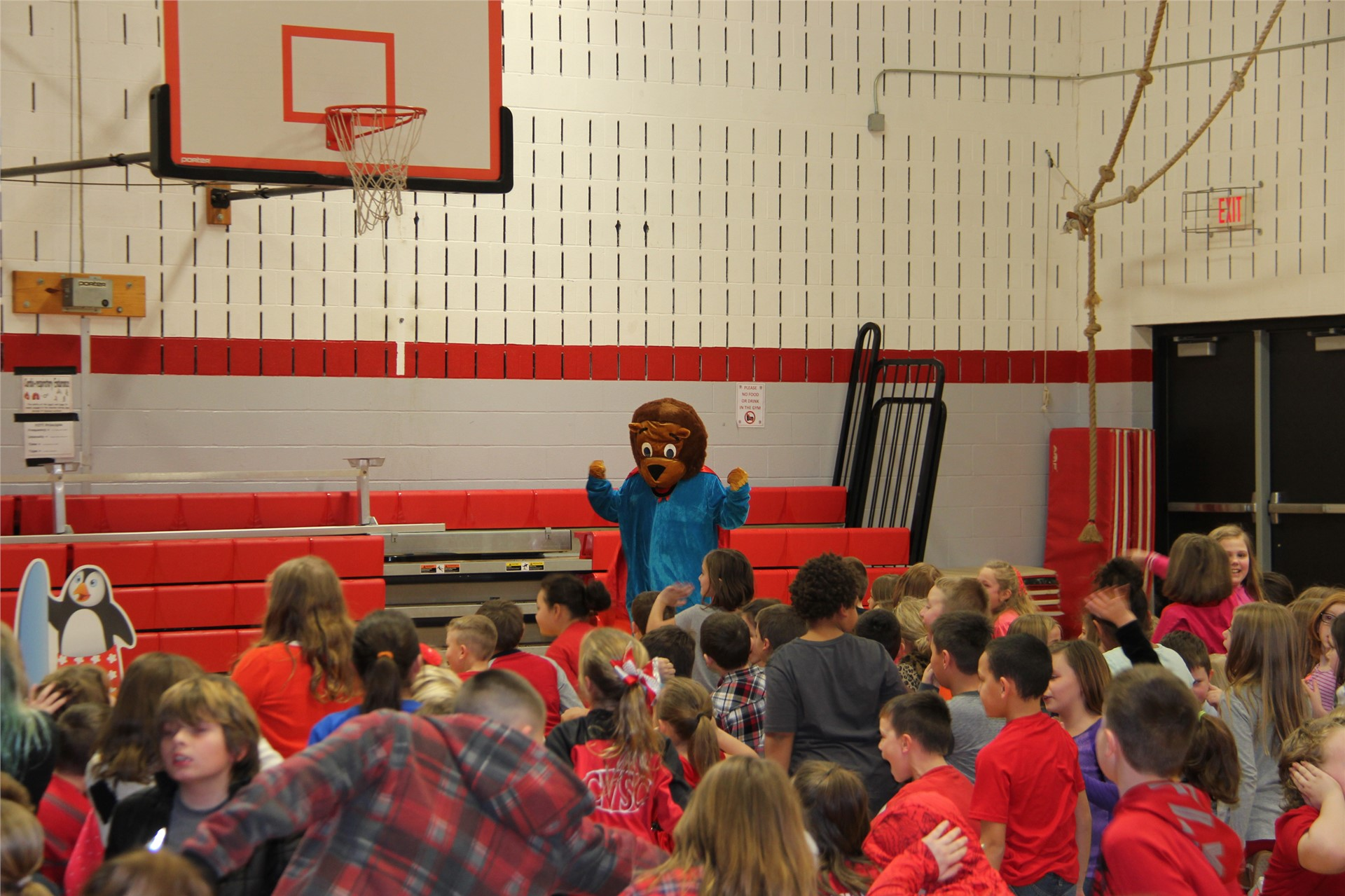 bear mascot stands in front of sitting students